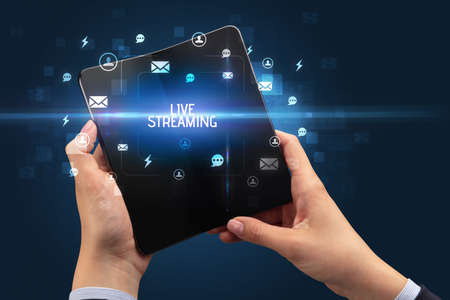 Businessman holding a foldable smartphone with LIVE STREAMING inscription, social networking concept