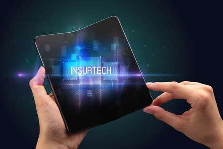 Businessman holding a foldable smartphone with INSURTECH inscription, new technology concept Foto de archivo