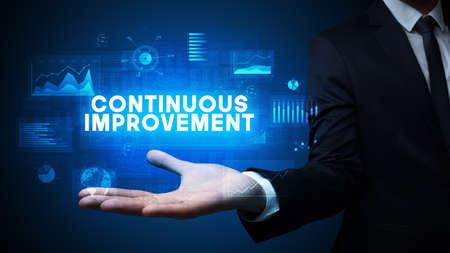 Hand of Businessman holding CONTINUOUS IMPROVEMENT inscription, business success concept