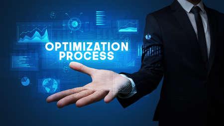 Hand of Businessman holding OPTIMIZATION PROCESS inscription, business success concept
