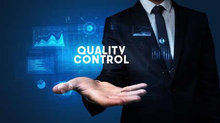 Hand of Businessman holding QUALITY CONTROL inscription, business success concept