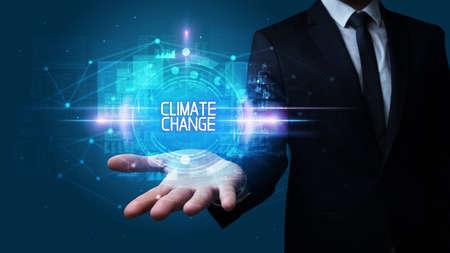 Man hand holding CLIMATE CHANGE inscription, technology concept Foto de archivo