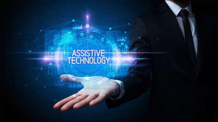 Man hand holding ASSISTIVE TECHNOLOGY inscription, technology concept Foto de archivo