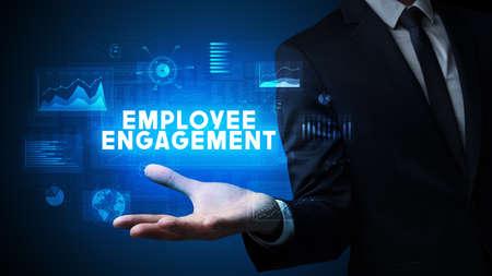 Hand of Businessman holding EMPLOYEE ENGAGEMENT inscription, business success concept