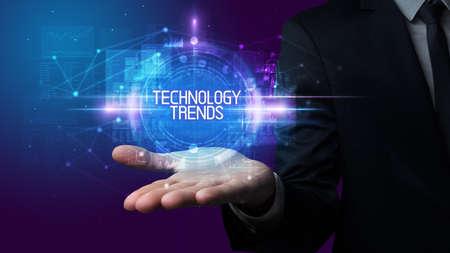 Man hand holding TECHNOLOGY TRENDS inscription, technology concept