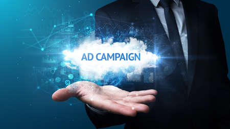 Hand of Businessman holding AD CAMPAIGN inscription, successful business concept