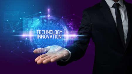 Man hand holding TECHNOLOGY INNOVATION inscription, technology concept Foto de archivo