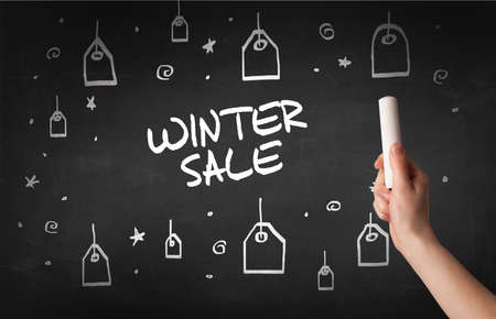 Hand drawing WINTER SALE inscription with white chalk on blackboard, online shopping concept