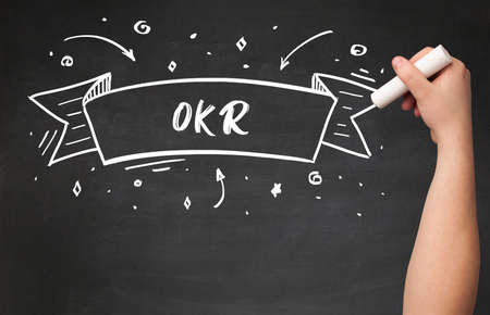 Hand drawing OKR abbreviation with white chalk on blackboard Stockfoto