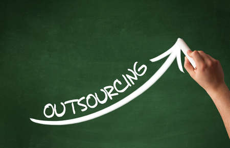 Hand drawing OUTSOURCING inscription with white chalk on blackboard, business concept