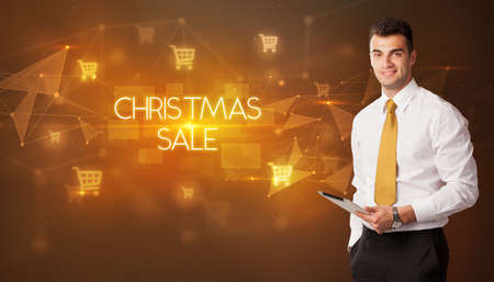Businessman with shopping cart icons and CHRISTMAS SALE inscription, online shopping concept