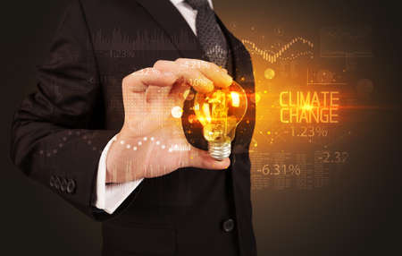 Businessman holding lightbulb with CLIMATE CHANGE inscription, Business technology concept