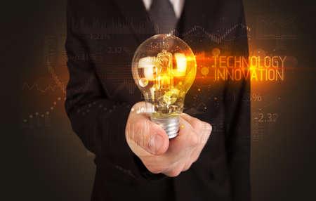 Businessman holding lightbulb with TECHNOLOGY INNOVATION inscription, Business technology concept Stockfoto