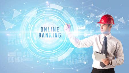 Handsome businessman with helmet drawing ONLINE BANKING inscription, contruction business concept Imagens