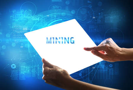 Hand holdig futuristic tablet with MINING inscription, new technology concept