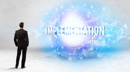 Rear view of a businessman standing in front of IMPLEMENTATION inscription, modern technology concept