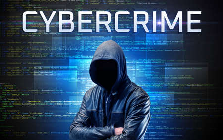 Faceless hacker with CYBERCRIME inscription on a binary code background