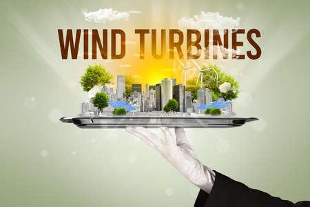 Waiter serving eco city with WIND TURBINES inscription, renewabke energy concept Archivio Fotografico