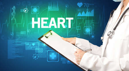 young doctor writing down notes with HEART  inscription, healthcare concept