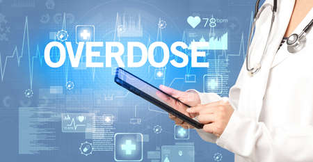 young doctor writing down notes with OVERDOSE  inscription, healthcare concept