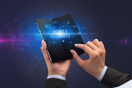 Businessman holding a foldable smartphone with MOBILE SECURITY inscription, cyber security concept