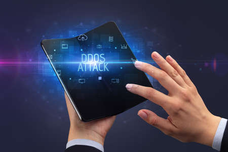 Businessman holding a foldable smartphone with DDOS ATTACK inscription, cyber security concept