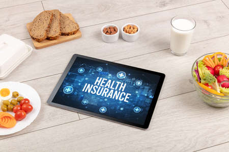 HEALTH INSURANCE concept in tablet pc with healthy food around, top view