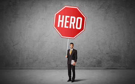 Young business person holding road sign with HERO inscription, new rules concept Banco de Imagens