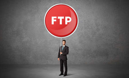 Young business person holdig traffic sign with FTP abbreviation, technology solution concept Reklamní fotografie