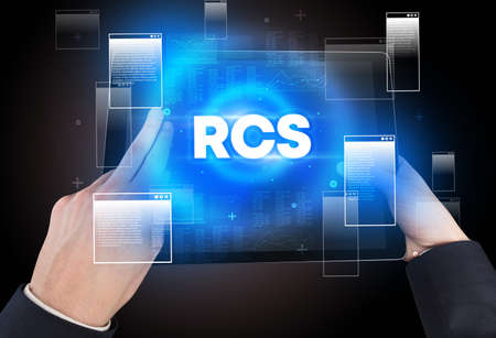 Close-up of a hand holding tablet with RCS abbreviation, modern technology concept