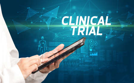 doctor writes notes on the clipboard with CLINICAL TRIAL inscription, medical diagnosis concept
