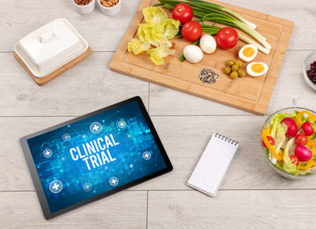 CLINICAL TRIAL concept in tablet pc with healthy food around, top view