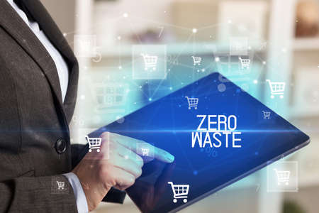 Young person makes a purchase through online shopping application with ZERO WASTE inscription Standard-Bild