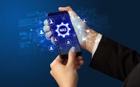 Female hand holding smartphone with NAS abbreviation, modern technology concept Banco de Imagens