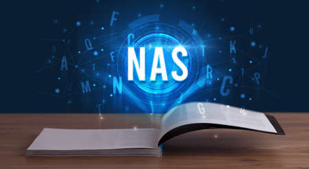 NAS inscription coming out from an open book, digital technology concept Banco de Imagens