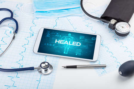 Tablet pc and doctor tools with HEALED inscription, coronavirus concept Imagens
