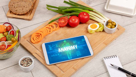 ANATOMY concept in tablet with fruits, top view