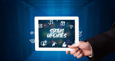 Young business person working on tablet and shows the inscription: STATUS UPDATES Stockfoto