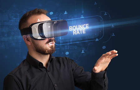 Businessman looking through Virtual Reality glasses with BOUNCE RATE inscription, social networking concept Imagens