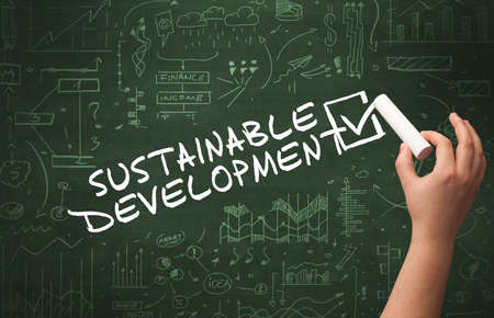Hand drawing SUSTAINABLE DEVELOPMENT inscription with white chalk on blackboard, new business concept Stock fotó