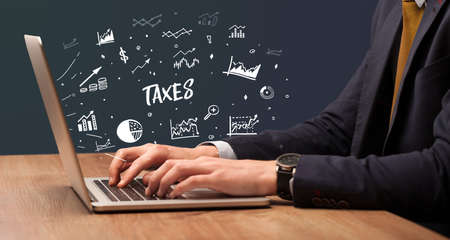 Businessman working on laptop with TAXES inscription, modern business concept
