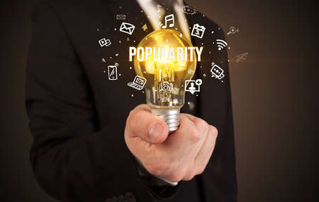 Businessman holding light bulb with POPULARITY inscription, social media concept Foto de archivo