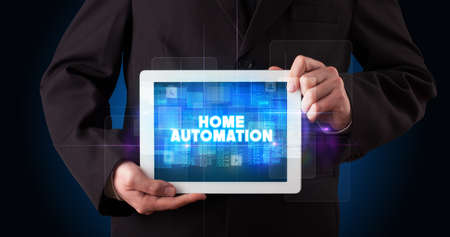 Young business person working on tablet and shows the inscription: HOME AUTOMATION