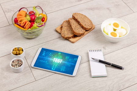 TEST concept in tablet with fruits, top view
