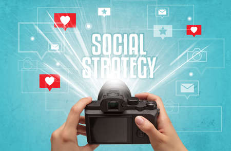 Close-up of a hand taking photos with SOCIAL STRATEGY inscription, social media concept