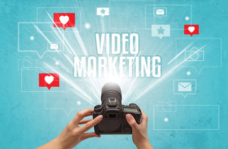 Close-up of a hand taking photos with VIDEO MARKETING inscription, social media concept