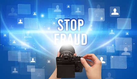 Close-up of hand holding camera with STOP FRAUD inscription, video surveillance concept