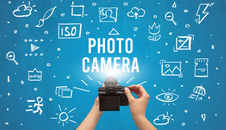 Hand taking picture with digital camera and PHOTO CAMERA inscription, camera settings concept