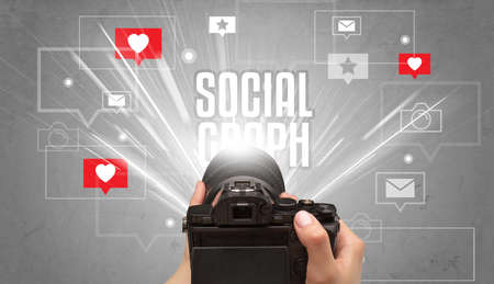 Close-up of a hand taking photos with SOCIAL GRAPH inscription, social media concept