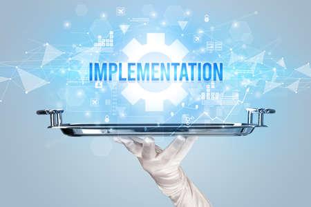 Waiter serving new technology concept with IMPLEMENTATION inscription Standard-Bild